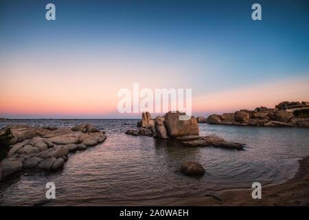 Pleine lune s'élève au-dessus de pierres juste à côté de la plage sur l'île de Cavallo dans l'archipel des Lavezzi juste au sud de la Corse en France Banque D'Images