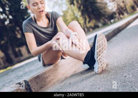 Focus sélectif de la sportive jeunes assis sur la jambe blessée et le touche Banque D'Images
