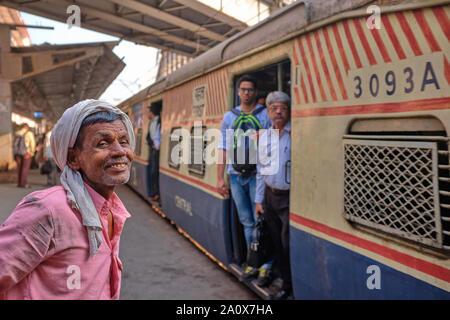 Un heureux porteur de Maharaj Chhatrapati Shivaji Terminus (CSMT) à Mumbai, Inde, en attente de l'arrivée d'un train local pour transférer ses biens