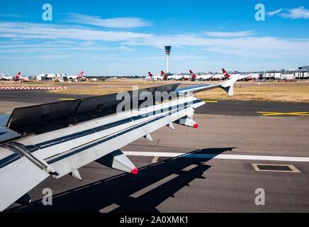 Vue depuis la fenêtre de l'avion sur l'atterrissage de l'aile sur la piste de l'aéroport avec des avions de Virgin Atlantic, Londres, Angleterre, Royaume-Uni
