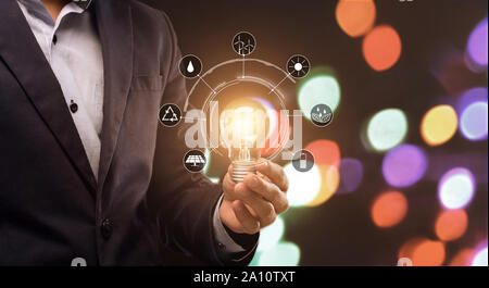 Businessman holding ampoule avec icônes de sources d'énergie
