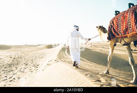 Homme portant des vêtements traditionnels, en tenant un chameau sur le sable du désert, à Dubaï Banque D'Images
