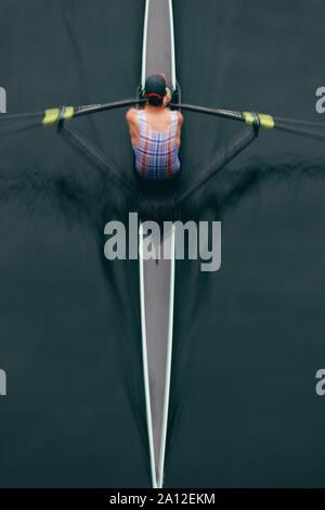 Vue aérienne d'un rameur en skiff bateau sur une eau calme, mi-course, de flou. Banque D'Images