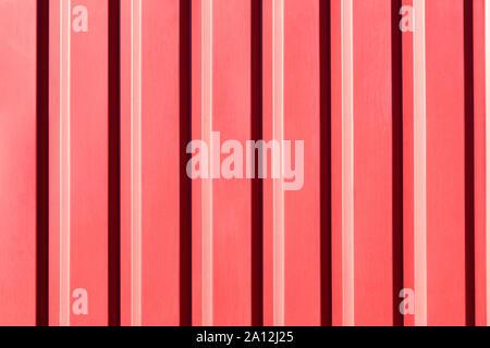 Clôture métallique rouge fait de tôle d'acier ondulée avec vertical guides et d'un gradient de soleil. Banque D'Images