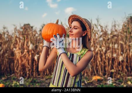 La récolte de citrouille. Jeune femme agriculteur récolte automne cueillette de citrouilles à la ferme. L'agriculture. L'action de grâce et de préparation de l'Halloween