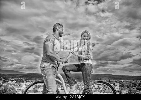 Homme avec barbe et dame blonde timide sur la première date. Comment satisfaire les filles alors qu'à vélo. Ramasser des fille. Couple tout juste de faire connaissance. Femme se sent timide en société avec macho attrayant. Banque D'Images