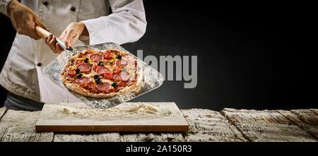 Chef de la suppression d'un salami italien pizza du four de l'afficher sur une palette métallique sur une planche en bois farinée dans un panorama rustique bannière avec copie Banque D'Images