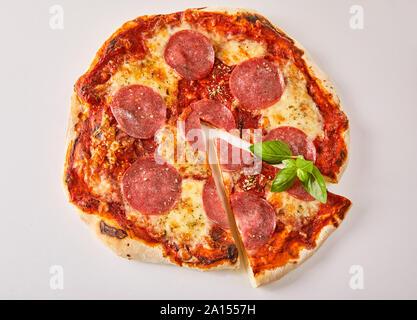 Vue aérienne d'un salami pizza traditionnelle Italienne avec une seule coupe tranche isolé sur blanc pour la publicité menu Banque D'Images