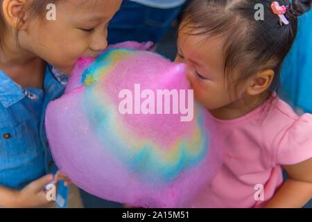 Heureux les enfants garçon et fille brother and sister eating cotton candy. Galerie d'images haute résolution. Banque D'Images