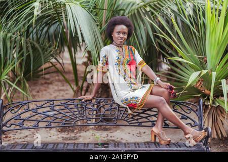 Jeune femme posant sur un banc parmi les plantes tropicales