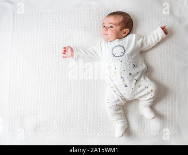 Baby Boy laying in bed plus de couverture blanche Banque D'Images