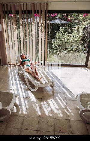 Young woman relaxing on lounge dans un spa Banque D'Images