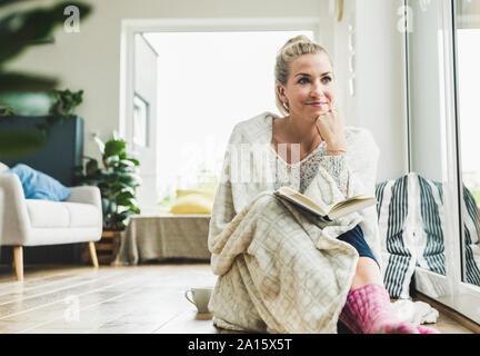 Femme enveloppée dans une couverture assis à la fenêtre à la lecture d'un livre