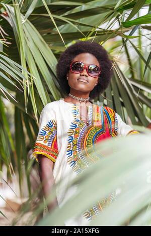 Cool jeune femme portant des lunettes posant parmi les plantes tropicales