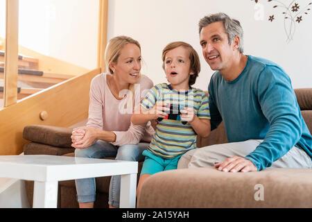 Les parents heureux avec son playing video game sur la table à la maison Banque D'Images