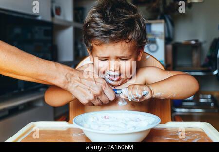 Little Boy eating yoghurt à la maison, main de femme sur la cuillère