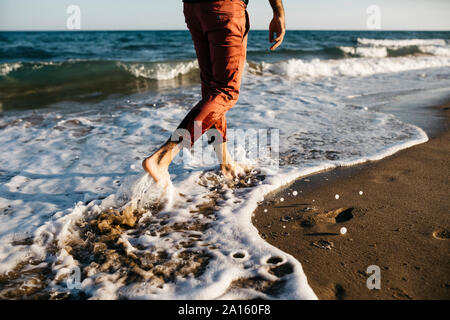 Vue arrière de l'homme avec un pantalon orange marche sur une plage au bord de l'eau Banque D'Images