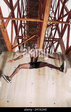 Young man jogging sous un pont Banque D'Images