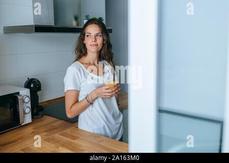 Jeune femme debout dans la cuisine avec un verre de jus d'orange