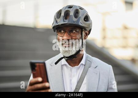 Portrait of smiling senior woman with smartphone portant des lunettes et casque de vélo Banque D'Images