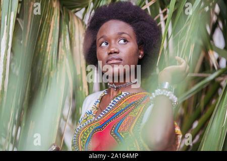 Jeune femme debout parmi les plantes tropicales Banque D'Images