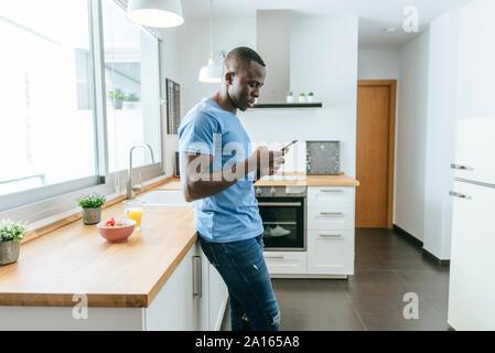 Young man using cell phone in cuisine à la maison Banque D'Images
