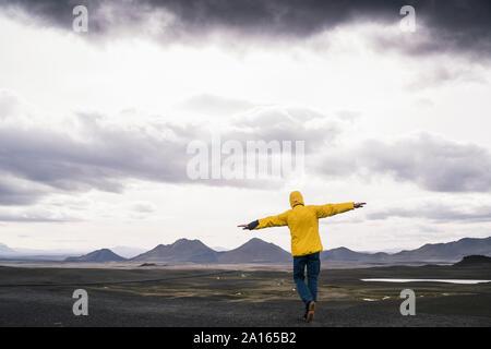 Man standing with arms out dans la région des hautes terres d'Islande