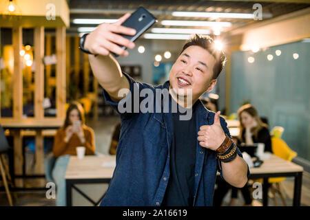 Moderne, élégant, joyeux chinois auto prise de photo sur l'appareil photo avant de son téléphone, smart phone, showing thumb up symbole, standing in modern Banque D'Images