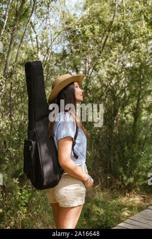 Jeune femme avec étui à guitare looking up Banque D'Images