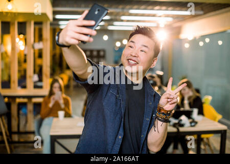 Moderne et convivial, élégant, gai homme asiatique libre prise de photo sur l'appareil photo avant de son téléphone, téléphone intelligent, montrant deux doigts, symbole de paix Banque D'Images