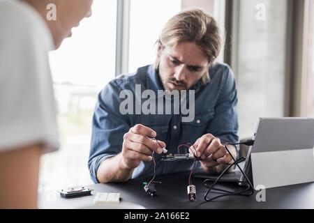 Jeune homme et femme travaillant sur le matériel informatique in office