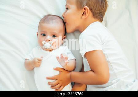 Frère aîné kissing baby boy in bed Banque D'Images