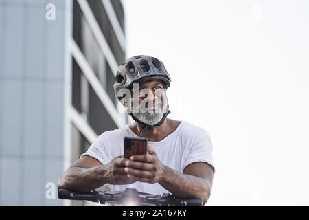 Portrait of happy young man wearing cycling helmet appuyée sur guidon de Scooter électrique
