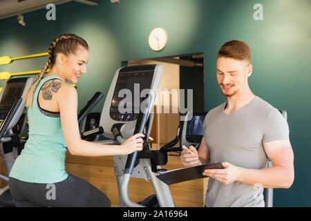 Jeune femme exerçant sur l'étape de la machine en salle de remise en forme avec entraîneur personnel à la prise de notes Banque D'Images