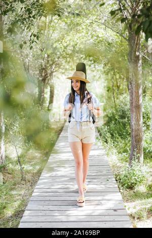 Jeune femme avec étui à guitare marche sur passerelle en bois Banque D'Images