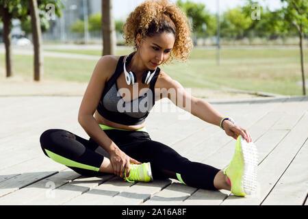 Sporty woman stretching dans le parc