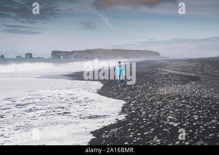 Jeune femme marche sur pieds nus sur une plage de lave en Islande