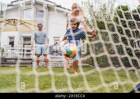 Happy Family playing football in garden Banque D'Images