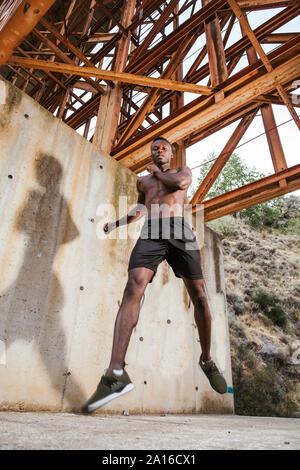 Jeune homme sautant sous un pont Banque D'Images