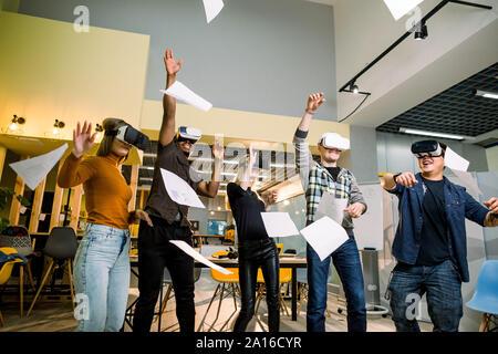 Groupe de jeunes gens portant des affaires multiraciale divers lunettes vr, jetant de documents, célébrer leur victoire in creative office loft moderne Banque D'Images