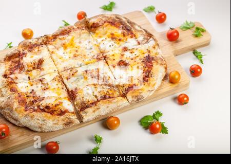 Pizza Quattro formaggi sur une planche à découper, tomates cerises et herbes Banque D'Images