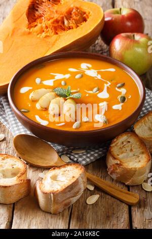 Soupe de potiron et de pomme avec des graines, du yaourt entouré par des ingrédients sur la table verticale.