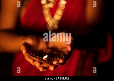 Happy Diwali - une belle femme ou une femme au foyer diya. Nouvelle mariée mariée vêtu du costume traditionnel saree et bijoux avec lampe à huile en terre cuite sur son ha Banque D'Images
