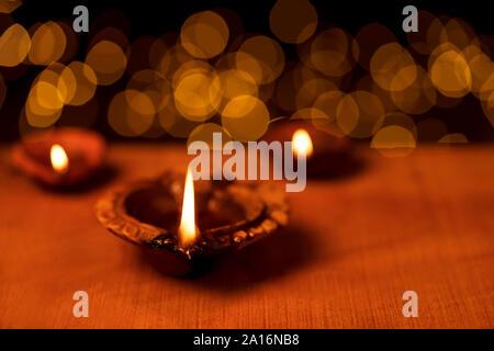 Diya argile lampes à huile allumé pendant diwali dans celebbration avec lumières bokeh fond noir foncé. Carte de voeux design for Indian Hindu festival lumière c Banque D'Images