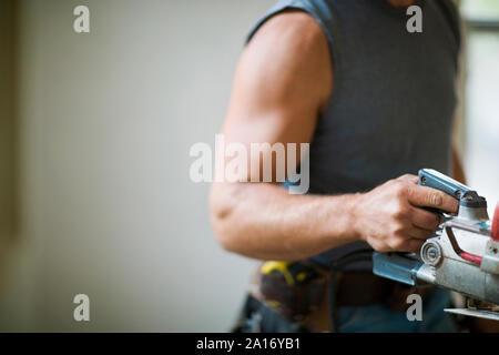 Constructeur mâle portant un outil de construction. Banque D'Images