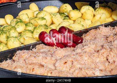 Plat traditionnel polonais avec de la saucisse, le chou et les pommes de terre Banque D'Images