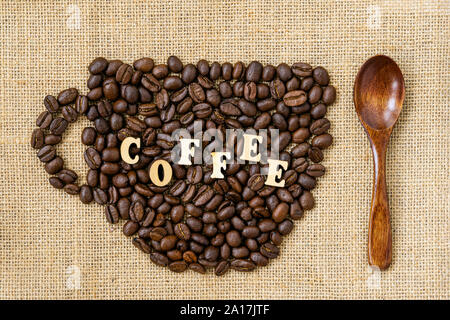 Les grains de café torréfiés tasse en forme de close-up avec word café et cuillère en bois naturel sur toile, sacs Banque D'Images