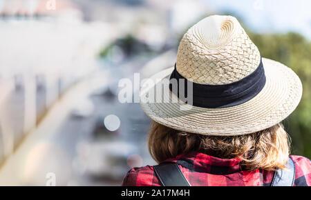 Une jeune femme dans son chapeau avec un sac à dos se tient sur un pont à pied et regarde la route Banque D'Images