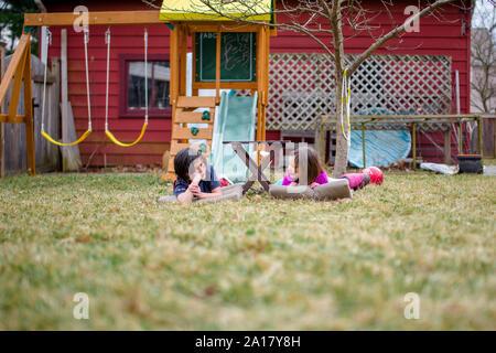 Deux heureux des enfants déposent sur des nattes dans leur cour bavardant ensemble