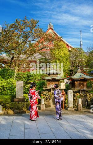 Tokyo entre tradition et modernité. Les jeunes filles japonaises et kimons holding mobile en pierre dans le vieux temple Asakusa avec la nouvelle de Skytree Banque D'Images